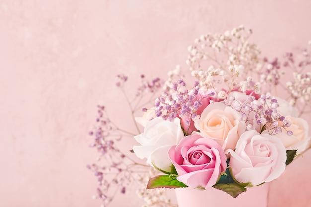 Composizione festiva con bellissimi fiori di rose delicate in scatola rotonda rosa su sfondo rosa chiaro. lay piatto, copia dello spazio. biglietto d'auguri.