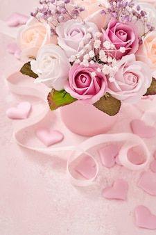 Composizione festiva con bellissimi fiori di rose delicate in scatola rotonda rosa su sfondo rosa chiaro. cartolina d'auguri di felice festa della mamma. lay piatto, copia spazio.