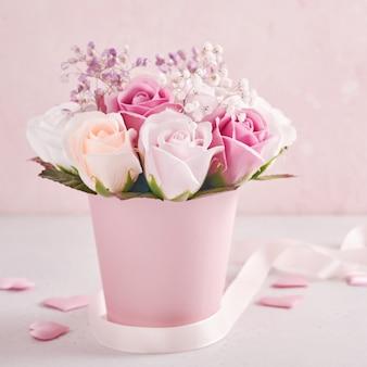Composizione festiva con bellissimi fiori di rose delicate in scatola rotonda rosa su sfondo rosa chiaro. cartolina d'auguri di felice festa della mamma. immagine quadrata.