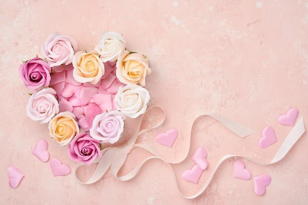 Composizione festiva con bellissimi fiori di rose delicate in scatola rotonda rosa su sfondo rosa chiaro.
