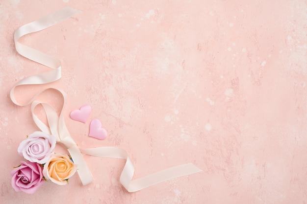 Composizione festiva con bellissimi fiori di rose delicate in scatola rotonda rosa sul tavolo rosa chiaro. lay piatto, copia dello spazio.
