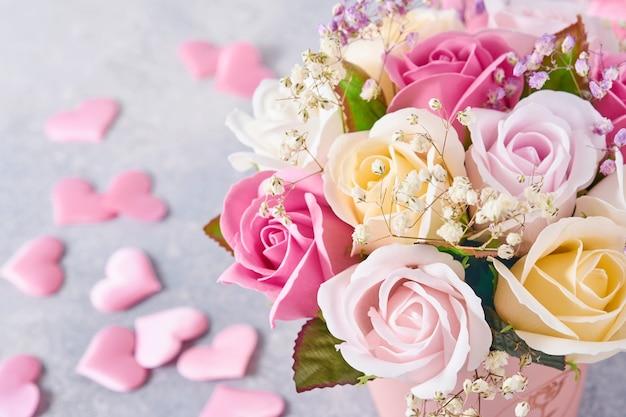 Composizione festiva con bellissimi fiori di rose delicate in scatola rotonda rosa con cuori rosa su sfondo grigio chiaro. lay piatto, copia dello spazio.