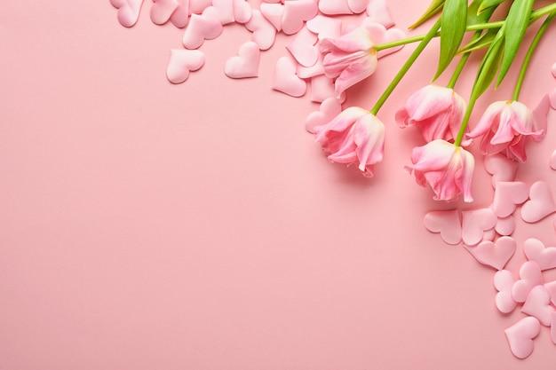 Composizione festosa con bellissimi fiori delicati di tulipani in una scatola rotonda rosa su sfondo chiaro