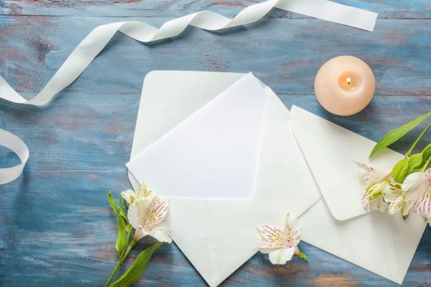 Composizione festiva con carta bianca e buste sulla tavola di legno