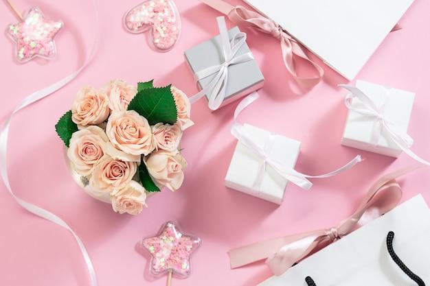 Composizione festiva con bouquet di rose rosa in vaso, decorazioni scintillanti, confezioni regalo