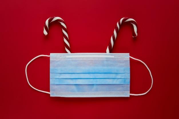 Renna festiva del coronavirus realizzata con maschera facciale e decorazioni su sfondo rosso. composizione piatta per le vacanze di natale vista dall'alto. banner di carta da parati di capodanno