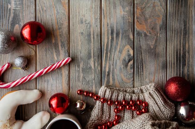 Festosa atmosfera natalizia accogliente. decorazioni per le vacanze su fondo in legno. palline di zucchero filato e maglione lavorato a maglia.