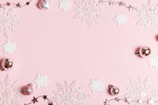Composizione festiva per le vacanze di natale in argento bianco creativo festivo, palla natalizia con decorazioni natalizie con nastro, fiocchi di neve su sfondo rosa. natale, inverno, concetto di capodanno. disposizione piana, vista dall'alto, copia spazio