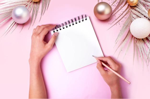 Decorazioni festive e mani che scrivono piani per l'anno in un taccuino. pianificazione di natale e capodanno