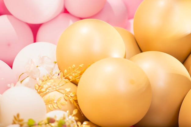 Area di decorazione festiva con grandi palloncini d'oro e fiori rosa per san valentino di matrimonio di compleanno