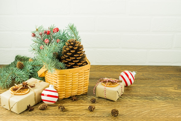 Decorazione festiva per la casa a natale. cesto di vimini con rami di abete e bacche, cono di cedro e scatole regalo su un tavolo di legno.