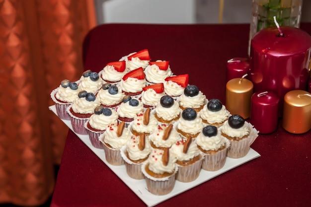 Design festoso di torte e candele di compleanno luminose su un tavolo rosso brillante