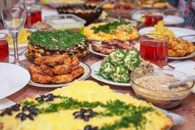 Cena festiva a casa, il giorno di natale. pancetta, palline di formaggio, pesce fritto in pastella, cotolette, purè di patate, torta di fegato, composta di frutta in un bicchiere e altro.