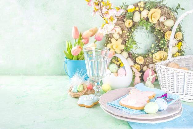 Regolazione festiva della tavola di pasqua con i tradizionali fiori primaverili, uova colorate di pasqua e biscotti di zucchero