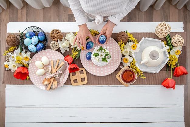 Tavola di pasqua festiva con torta di pasqua fatta in casa, tè, fiori e dettagli di arredamento copia spazio. concetto di celebrazione della famiglia.