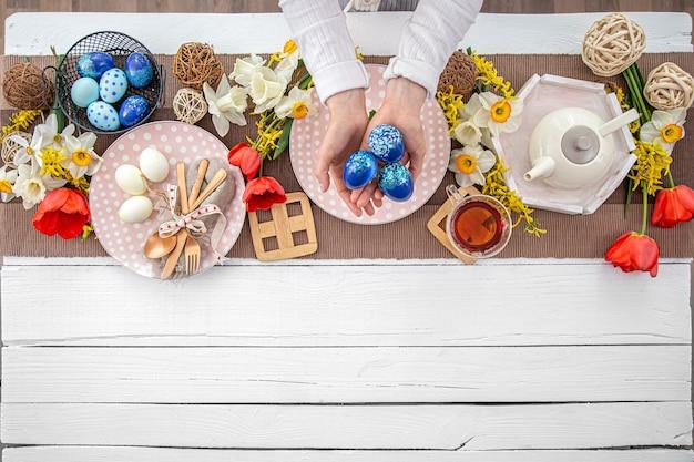 Tavola di pasqua festiva con torta di pasqua fatta in casa, tè, fiori e dettagli di arredamento copia spazio concetto di celebrazione della famiglia.