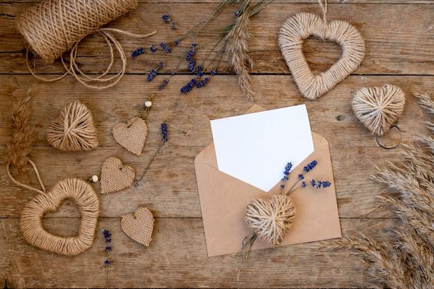 Festosa laici piatta per il giorno di san valentino dalla decorazione fai da te. cuori di iuta, fiori di lavanda, busta di carta artigianale. concetto di san valentino a rifiuti zero e mock up.