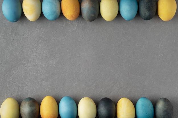 Festosa laici piatta con colorate tinte naturalmente le uova di pasqua su uno sfondo grigio, copia dello spazio