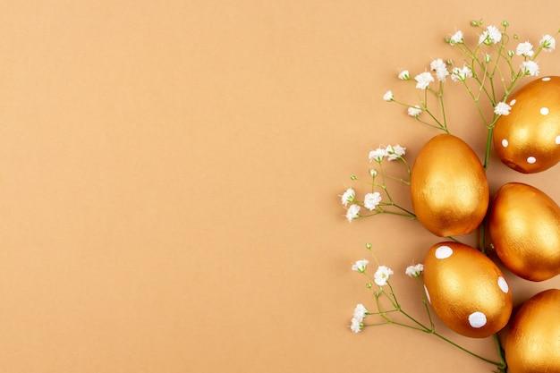 Piatto festivo laici con uova di pasqua dorate e fiori di gypsophila su sfondo marrone