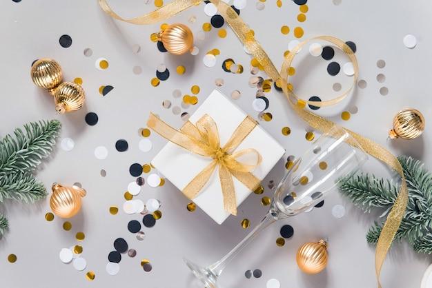 Piatto festivo con decorazioni di capodanno coriandoli e bicchieri di champagne su sfondo grigio