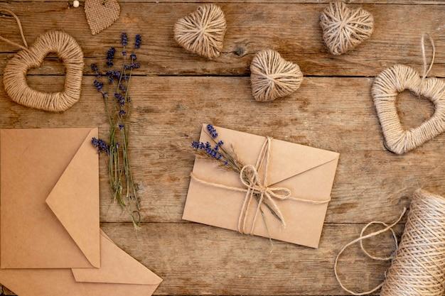Festosa categoricamente per il giorno di san valentino sul tavolo di legno. buste beige di carta artigianale decorate con fiori di lavanda e corda di iuta. san valentino a rifiuti zero