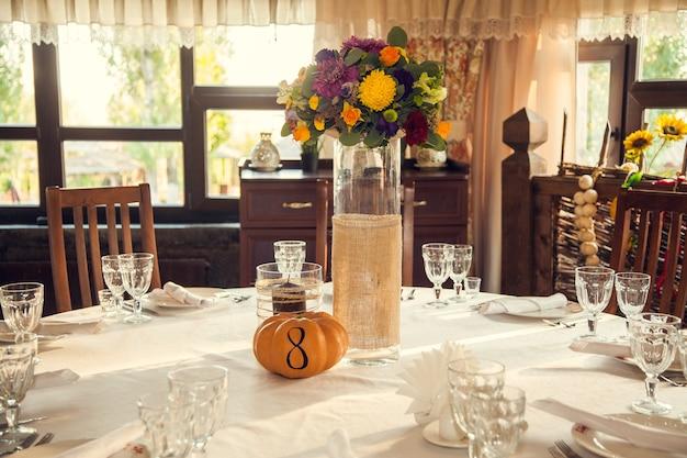 Fiorai festosa in stile autunnale con numerazione dei tavoli sulle zucche nella sala banchetti.