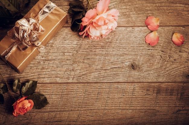 Fiori festosi rosa arancio e composizione regalo su fondo di legno rustico. vista dall'alto, piatta. copia spazio. compleanno, mamma, san valentino, donna, concetto di giorno delle nozze. atmosfera autunnale