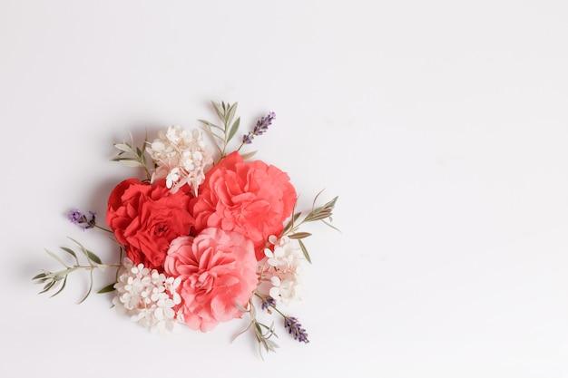 Begonia rossa dei fiori festivi, composizione bianca dell'ortensia sui precedenti bianchi. vista dall'alto, piatta. copia spazio. concetto di compleanno, festa della mamma, san valentino, donna, giorno del matrimonio