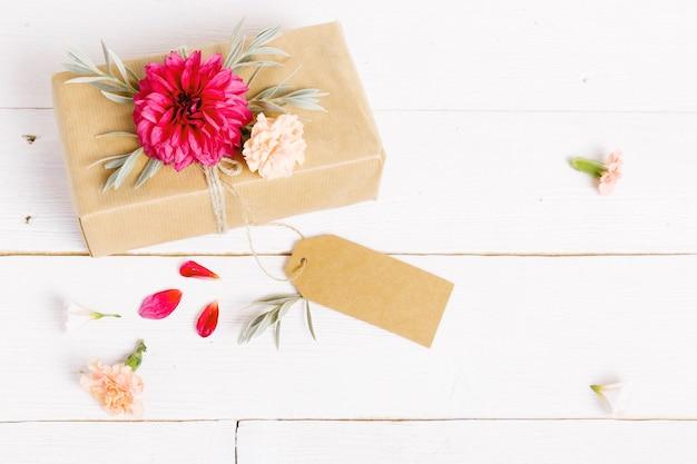 Composizione di dalie rosse di fiori festosi con un regalo sullo sfondo bianco