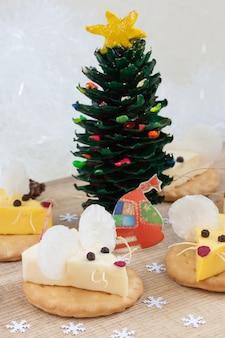 Cibo festivo per il nuovo anno 2020 - anno del ratto bianco (topo). antipasto di formaggio su un cracker. tradizione cinese.