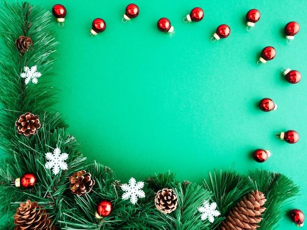 Cornice festosa di albero di natale, decorazioni natalizie, coni e giocattoli di natale su uno sfondo verde, copyspace, vista dall'alto.