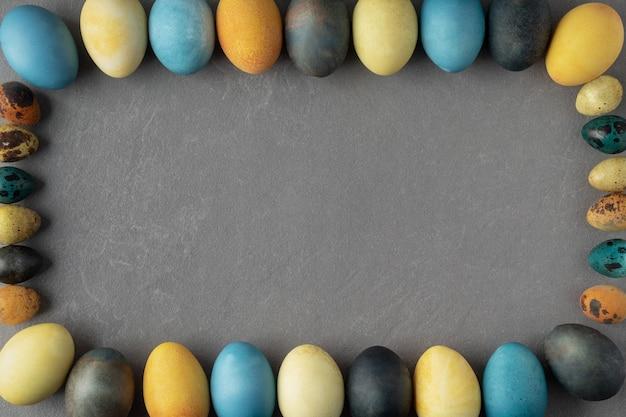 Cornice festosa con uova di pasqua colorate naturalmente sul tavolo grigio, spazio per il testo.