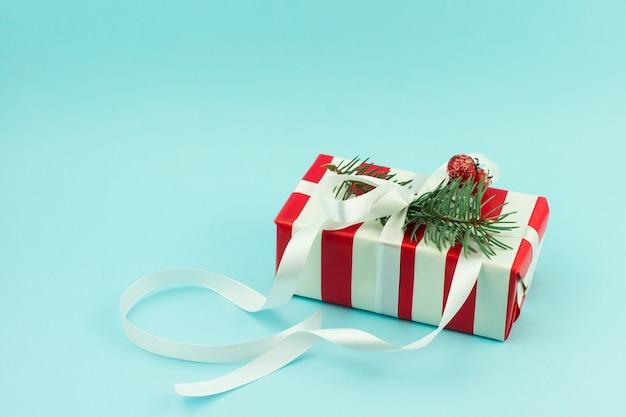 Regalo festivo in confezione luminosa con decorazione con nastro bianco con ramo di abete e bacche. vista frontale. una copia dello spazio.