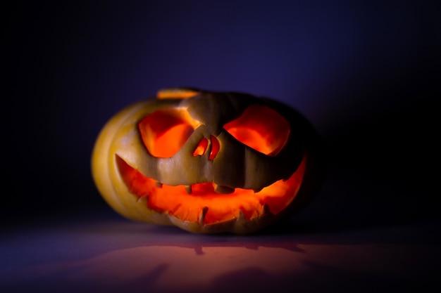 Zucca incandescente festiva per halloween su uno sfondo scuro.