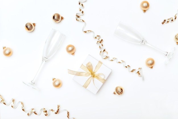 Festosa scatola regalo piatta in oro con bicchiere di champagne e palline di natale decorative sfondo bianco