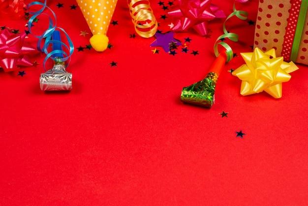 Festive stelle dorate e viola di coriandoli e un regalo, tappi di compleanno su sfondo rosso. spazio per testo o design.