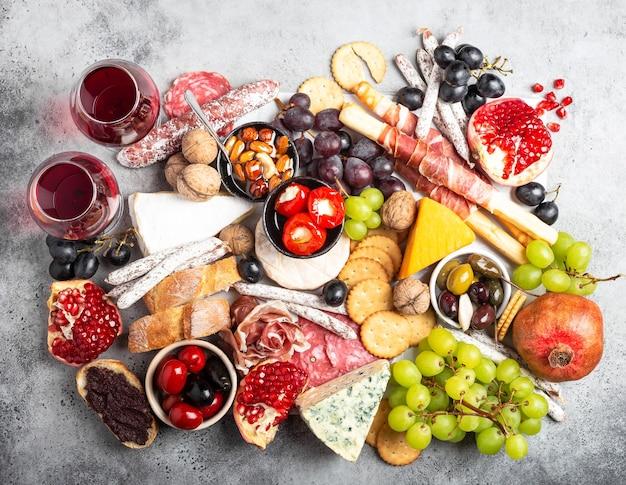 Mix festoso gourmet di snack e antipasti, formaggio, carne, olive, pane, frutta, tartine, vino in bicchieri. set di antipasti italiani o bar di tapas spagnole. cibo da condividere, festa o picnic, vista dall'alto