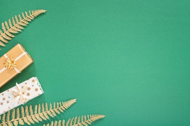 Sfondo verde festivo con decorazioni in oro, sfondo con foglie di felce dorate lucide glitter e confezioni regalo, vista piana, vista dall'alto