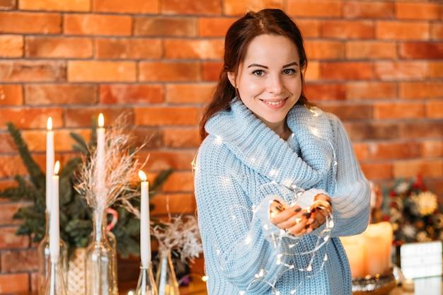 Decorazioni interne festive. ritratto di signora felice che tiene le lucine.
