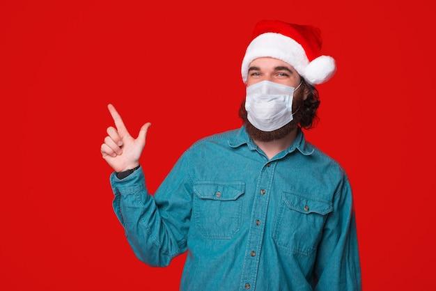 Mand festivo indossando un cappello da babbo natale e proteggersi con una maschera, indicando lontano su sfondo rosso