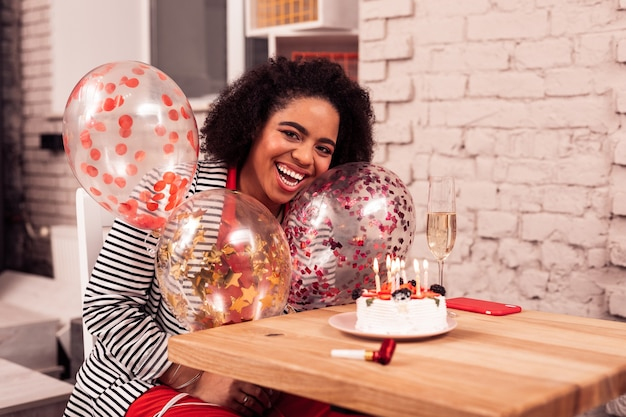 Atmosfera festosa. felice donna afro-americana che tiene palloncini colorati pur essendo in uno stato d'animo festoso