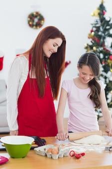Madre festiva e figlia che cuociono insieme