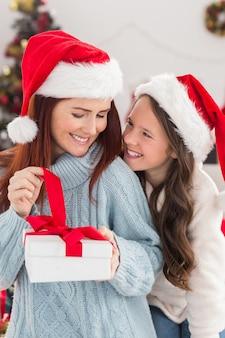 Festiva madre e figlia sul divano con regalo