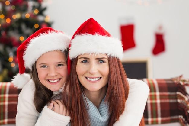 Madre e figlia festive che sorridono alla macchina fotografica