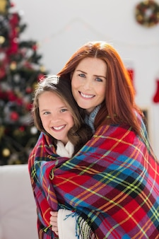 Festiva madre e figlia avvolta in coperta