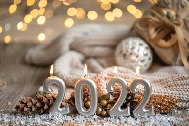 Fondo festivo del nuovo anno con le candele sotto forma dei numeri 2022
