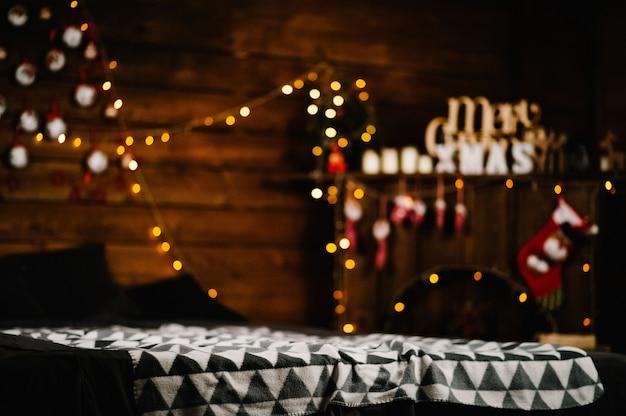 Decorazioni festive di capodanno in camera. divano, caminetto, stelle e luci. felice anno nuovo 2019 e buon natale.