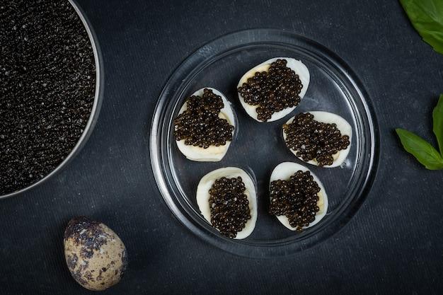 Capodanno festivo. panini con storione caviale nero su un piatto rotondo blu su una superficie scura.