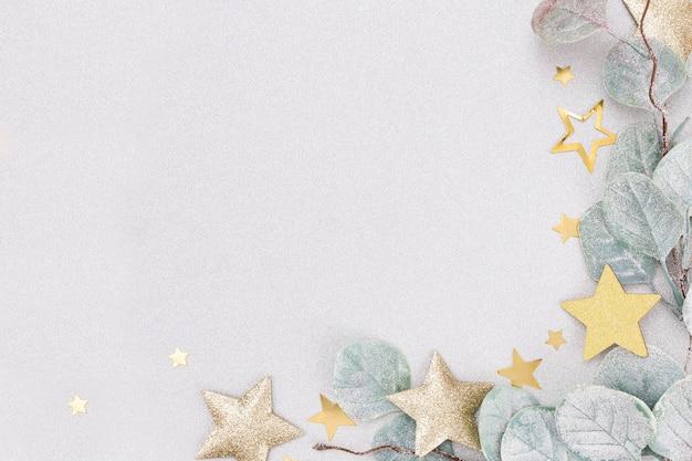 Sfondo pastello festivo. stelle di natale e brillantini, coriandoli su sfondo pastello. sfondo di natale, piatto disteso.