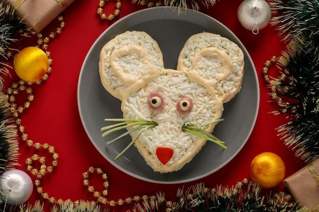 Insalata festiva mouse su sfondo rosso, cibo simbolico per il nuovo anno, primo piano, vista dall'alto, orientamento orizzontale